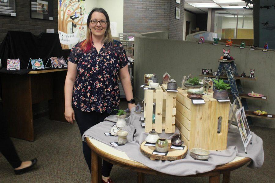 Ceramics teacher, Mrs. Wartenburg next to one her showcased pieces.