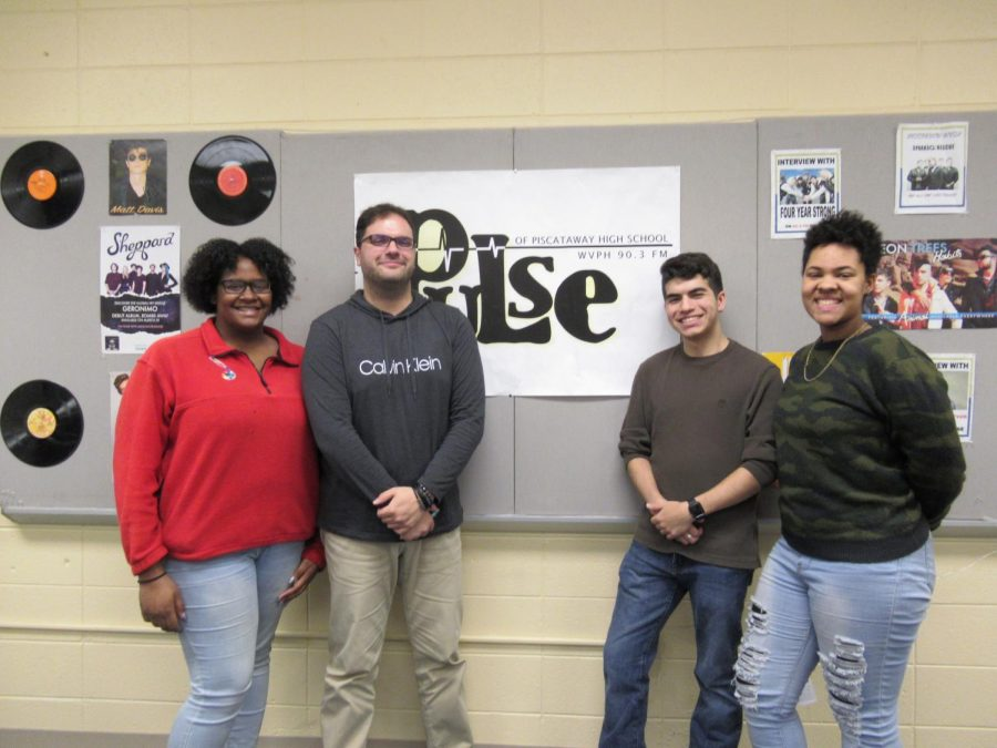 Mr. Giannino posing with the radio club members in front of the wall in the second recording room