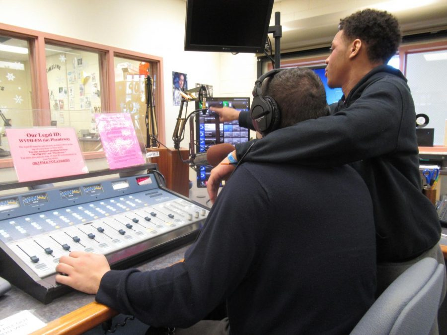 A student helps Mr. Giannino pick out songs for the radio to play.