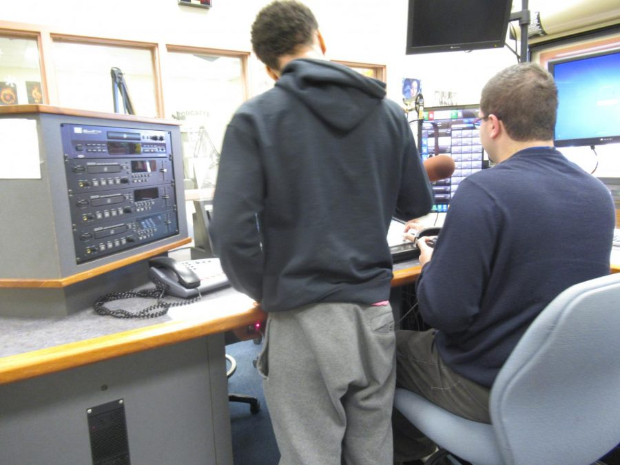 Mr. Giannino works with a student in one of his classes---showing him how the equipment works