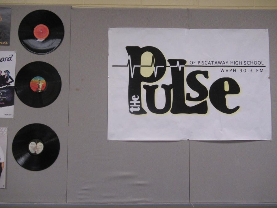 A wall containing a sign of the station, and more record decor. A picture of every student who has been in the club lies behind the cover according to Giannino.