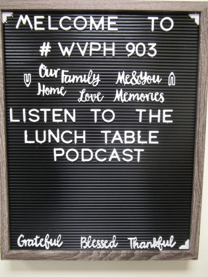 A sign welcomes people to the studio and advertises on of their podcasts The Lunch table podcast
