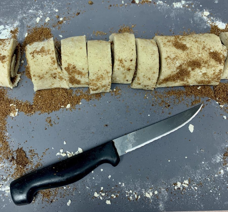 Beginning at the long end, tightly roll the dough into a log. Trim off the edges then slice the log into about 9 rolls.