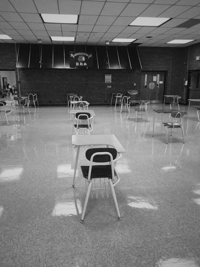 The cafeteria looks a little different in hybrid lunch. During lunch, instead of large tables being placed around the room there are now singular desks to maintain social distancing. This was during an active lunch period and the cafeteria is almost empty.